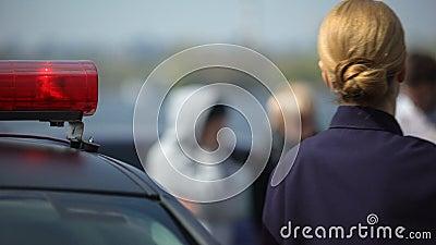 Женщина-полицейский приезжая на место преступления, выходить автомобиля и идти к заверителям сток-видео
