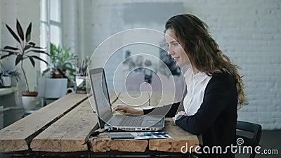 Женщина посылая сообщение мобильным телефоном и работая компьтер-книжкой видеоматериал