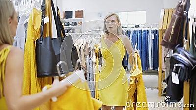 Женщина приспосабливая желтое платье в бутике Модная и стильная девушка оставаясь перед зеркалом Детеныши и акции видеоматериалы