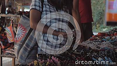 Женщина пробует на покрашенных браслетах в азиатском уличном рынке Продажа браслетов в рынке видеоматериал