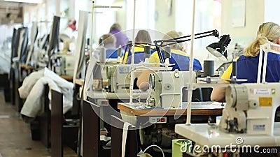 Женщина работая на швейной машине, промышленная фабрика ткани размера, работники на производственной линии, промышленном интерьер сток-видео