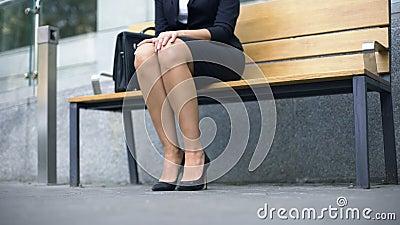 Женщина сидит вниз на стенде, утомленном идти в дискомфортные высоко-накрененные ботинки сток-видео