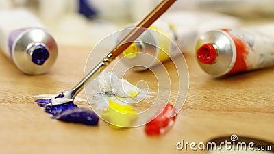 Женщина смешивает краски на палитре бело Красный bluets yellow Краски масла Палитра красок Художник подготавливает краски акции видеоматериалы