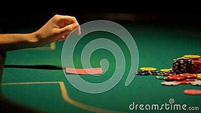 Женщина сомневаясь но кладя деньги на таблицу покера, надежды выиграть, играя в азартные игры везение видеоматериал