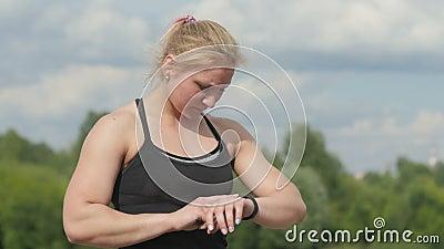 Женщина спорта здоровья нося умный прибор дозора с экраном касания делая тренировки сток-видео