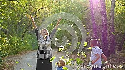 Женщина с детьми бросает вверх листья видеоматериал