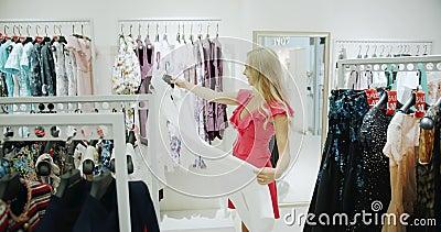 Женщина с одеждой в магазине акции видеоматериалы
