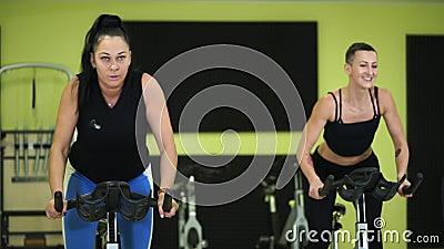 Женщины приниманнсяая за тренировка велосипеда группы для поддержания физического здоровья сток-видео