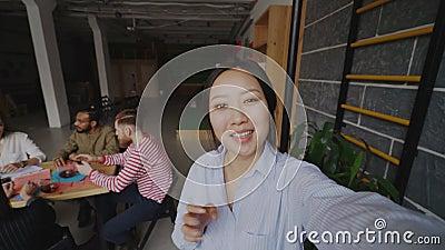 Жизнерадостная азиатская женщина держа smartphone и имеет onlive видео- звонок пока ее коллеги работая в современном офисе сток-видео