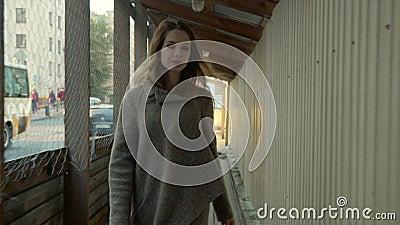 Жизнерадостная девушка идет в деревянное проходит дальше улицу города с плотным движением в осени акции видеоматериалы