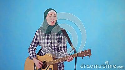 Жизнерадостная молодая мусульманская женщина выразительно играя гитару на голубой предпосылке акции видеоматериалы