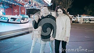 Жизнерадостная семья идет город ночи Родители соединили дочь к парку атракционов на весел-идти-круглой сток-видео