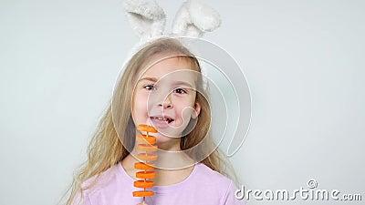 Зайчик девушки нося уши ест куски моркови видеоматериал