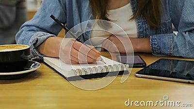 Закройте вверх по рукам женщины держа smartphone и писать с карандашем в тетради в кафе сток-видео