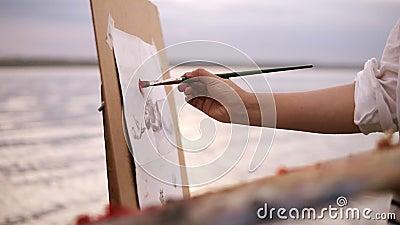 Закройте вверх процесса искусства ` s художника Мольберт и палитра Девушка кладет некоторые краски цвета на холст Запачканное озе сток-видео
