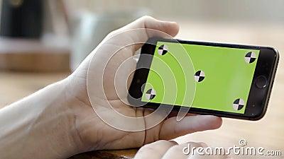 Закрытие телефона, удерживаемого рукой, горизонтально с зеленым экраном Съемка склада Человек держит телефон в горизонтальном пол сток-видео
