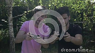 Замедленное движение 2 молодых друзей пристрастившийся к видео- игре играя с регуляторами в снаружи парка - видеоматериал