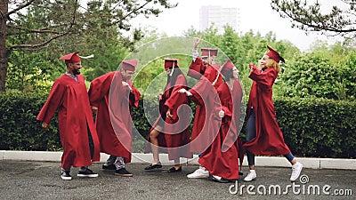 Замедленное движение шаловливых девушек и студентов парней градуируя танцуя, смеясь над и имея потеха на выпускном дне красивейше акции видеоматериалы