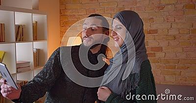 Заново купленный всход крупного плана молодых жизнерадостных мусульманских пар имея видео- звонок на планшете и показывая их видеоматериал