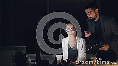 Занятые молодые люди мужчины и женские коллеги работают в офисе вечером говоря и смотря экран компьютера ванта видеоматериал