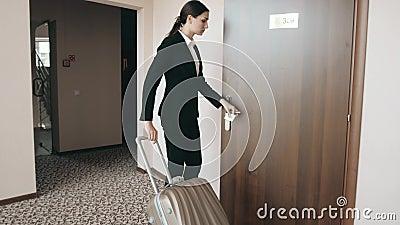 Задний портрет взгляда бизнес-леди в костюме юбки на высоких пятках идя с ее чемоданом вдоль лобби гостиницы видеоматериал