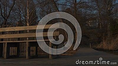 Золотой светлый заход солнца показывая стенд и деревянную палубу на стороне озера сток-видео