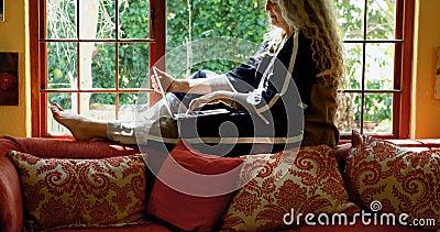Зрелая женщина используя компьтер-книжку около окна 4k акции видеоматериалы