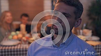 Зрелый заботливый человек, сидящий на переднем плане спиной к шумной компании молодых людей, празднующих праздник видеоматериал