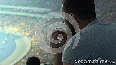 Игра спорта мужского сторонника наблюдая на агитированном стадионе, сконцентрированном и, беспокойство сток-видео