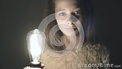 Идея приходила верно! Освещена электрическая лампочка в руке красивой маленькой девочки сток-видео