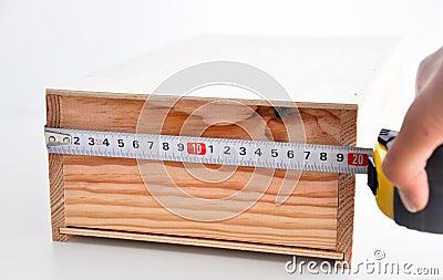 Измерять коробку с рулеткой