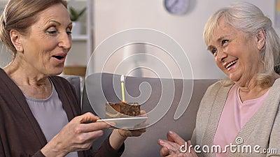 Именниный пирог пожилой женщины gifting к другу, даме делая желание и свечу дуновений сток-видео
