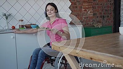 Инвалидная женщина, принимающая огурец и надевающая на стол в кухне акции видеоматериалы