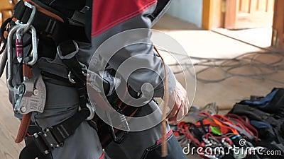 Индустриальный альпинист вводит оборудование для выполнения высокогорных работ на карабинерах альпинистского пояса видеоматериал