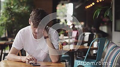 Интернет молодого человека занимаясь серфингом в мобильном телефоне, сподручном касании и текстовом сообщении отправки в кафе Кра видеоматериал