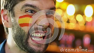 Испанский футбольный болельщик с флагом на щеке радуясь любимая победа команды, лига видеоматериал