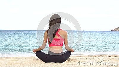 Йога молодой женщины практикуя на пляже на заходе солнца Тренировки штиль и сработанность Раздумье в представлении лотоса Здорово видеоматериал