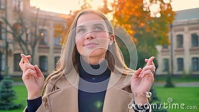 Кавказская девушка на открытом воздухе, стоит изолированной со спокойным счастливым взглядом и желать везение с ее пальцами перес сток-видео