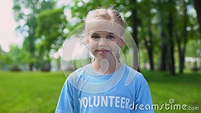 Кавказский ребенок-доброволец улыбается на камеру, зеленый лес, экосистема видеоматериал