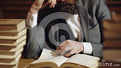 Кавказское мужское чтение, поворачивая страницы книги, пук книги в таблице Бородатая книга чтения человека на деревянном столе сток-видео