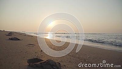 Камера движется по спокойному песчаному пляжу Средиземные волны, катающиеся к песку на закате Прекрасный рассвет в Турции акции видеоматериалы