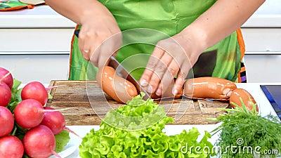Кашевар делит сосиски в естественной раковине сток-видео