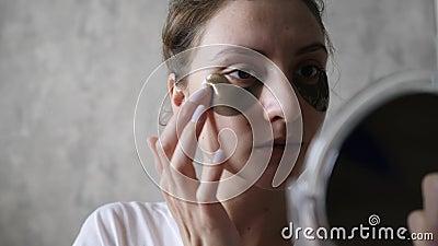Кожа под глазами - использование натуральной косметики здоровой девочкой, которая смотрит на себя в зеркало акции видеоматериалы