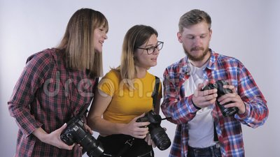 Компания профессионалов с цифровыми фотоаппаратами в руках, изучающих фотографии, сделанные в фотостудии во время семинара для сток-видео
