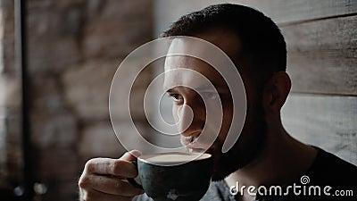 Конец-вверх мужественного человека с щетинкой и татуированными руками выпивая кофе в кафе видеоматериал