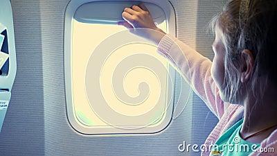 Конец-вверх Ребенк девушка поднимает занавес иллюминатора в кабине самолета, от там светит яркому свету девушка шикарная сток-видео