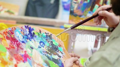 Конец-вверх рук ` s художника держит щетку и палитру Притяжка в красках в студии холстина видеоматериал
