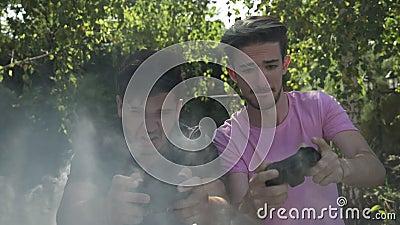 Конкуренция между 2 игроками молодого человека с кнюппелем пристрастившийся при видеоигры консоли предусматриванные в дыме в заме видеоматериал