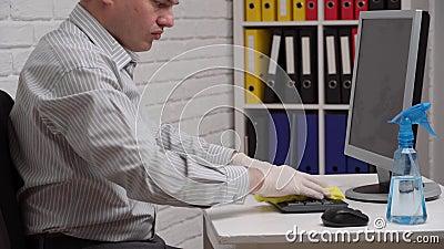 концепция очистки или дезинфекции офиса - бизнесмен очищает рабочее место, компьютер, стол, использует брызгозащитный пистолет и  акции видеоматериалы
