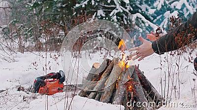 костры Разожженный огонь в человеке леса a зимы сидит огнем и нагревает их руки Цепная пила лежа на видеоматериал